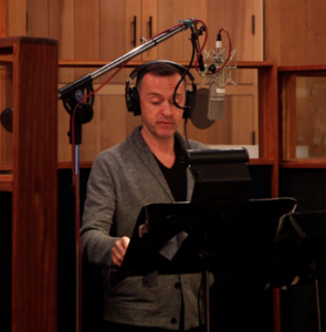 Andrew Lippa behind a microphone in the recording studio for The Man in the Ceiling